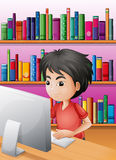 A boy playing computer in front of the shelves with books Royalty Free Stock Image