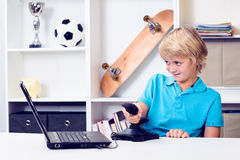 Boy is playing computer game. Blond boy is playing computer game in his room Royalty Free Stock Photos