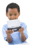 Boy playing computer game, father in background, cut out Stock Images