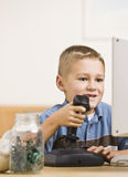 Boy Playing Computer Games. A young boy is playing computer games.  He is smiling and looking at the screen.  Vertically framed shot Royalty Free Stock Images