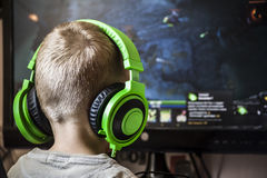 Boy playing computer. Boy in headphones playing a computer game Stock Photography