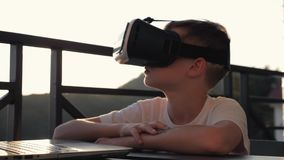 The boy is playing on the computer in virtual reality glasses in the sunset at sunset. The concept of modern. Technology and virtual life. Slow motion