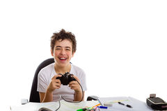 Boy playing with console controller and homework Stock Photos