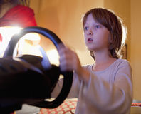 Boy Playing Console Game. Boy Playing Racing Console Game with Steering Wheel Stock Images
