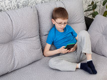 Boy playing on a console. Little boy in glasses laying on the sofa and playing on a console Royalty Free Stock Image