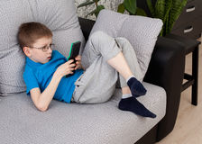 Boy playing on a console. Little boy in glasses laying on the sofa and playing on a console Stock Photography