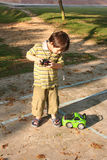 Boy playing control car. Boy playing green remote control car at the children playground Royalty Free Stock Image