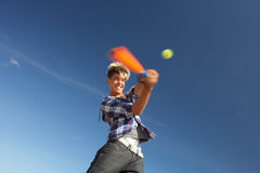 Boy playing cricket on beach Stock Images