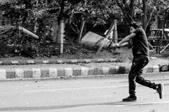Boy playing cricket on the street. Gurgaon, India - 13th April 2014: Boy hitting a cricket shot on the street. Cricket is a popular pastime in India. People tend Stock Photos