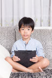Boy playing digital tablet Stock Photo