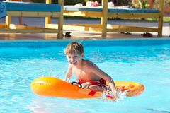 Boy playing on dingy in pool. Happy young boy playing on inflatable boat or dingy in swimming pool Stock Images