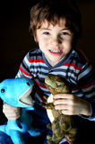 Boy Playing With Dinosaurs. A preschool aged boy wearing a red, gray, white and black striped shirt playing with two stuffed dinosaurs.  One is blue and the Royalty Free Stock Photo
