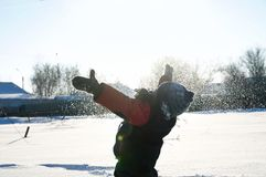 Boy playing dispersing snow in the air, outdoor children activity in winter cold. Happy childhood having fun Royalty Free Stock Photo
