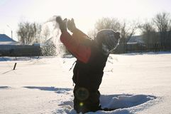 Boy playing dispersing snow in the air, outdoor children activity in winter cold. Happy childhood having fun Royalty Free Stock Image