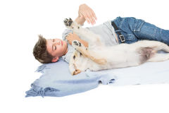 Boy playing with dog while lying on blanket Royalty Free Stock Photography