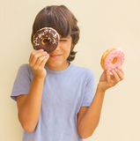 Boy playing with  donuts Royalty Free Stock Photos