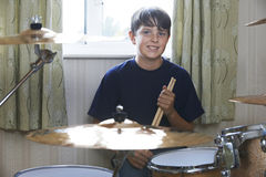 Boy Playing Drum Kit At Home Stock Image