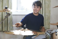 Boy Playing Drum Kit At Home Stock Photos
