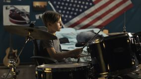 Boy playing drums in bedroom. Focused teen sitting in chair and playing drums with drumsticks in modern bedroom at home stock video