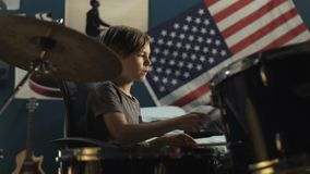 Boy playing drums in bedroom. Handheld shot of focused teen sitting in chair and playing drums with drumsticks in modern bedroom at home stock footage