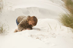 Boy playing in the dunes. Boy sitting in the dunes, playing in the sand Royalty Free Stock Photos