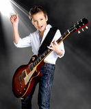 Boy playing on electric guitar on the stage Royalty Free Stock Photography