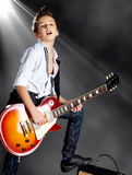 Boy playing on electric guitar on the stage Royalty Free Stock Photos