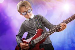 Boy playing electric guitar in talent show on stage. Boy playing electric guitar on stage in rock music school talent show Royalty Free Stock Photos
