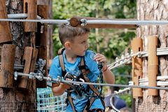 Sports kid in the forest. Little boy on a rope park for children. Plays in a place for family fun, entertainment and adventure. royalty free stock photos