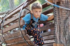 Little boy on a rope park for children. Plays in a place for family fun, entertainment and adventure. Boy playing extreme movement stock photos