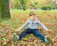 Boy playing with fallen leaves Stock Images