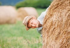 Boy playing on the field with hay rolls Royalty Free Stock Photo