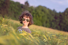 Boy playing on the filed in sunset, sunglasses Stock Image