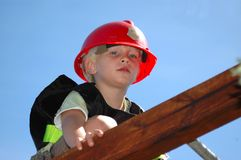 Boy playing firefighter. A beautiful little blond and blue eyed boy child head portrait with cute expression in the handsome face dressed up with a red helmet Royalty Free Stock Photography