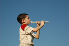 Boy playing the flute Stock Photography