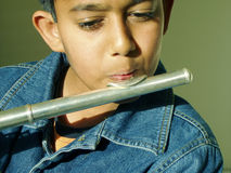 Boy playing flute. A young boy playing flute royalty free stock image