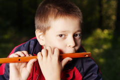 Boy playing flute in dark forest Royalty Free Stock Photography
