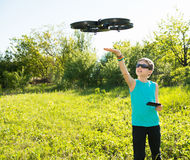 Boy playing with flying drone with camera controlled by smartphone stock photo