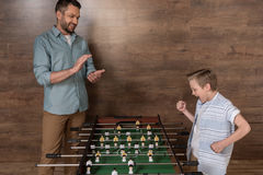 Boy playing foosball together with father Stock Photos