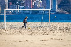 Boy playing football on the beach.  Royalty Free Stock Photography