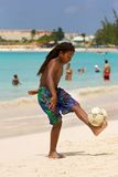 Boy playing football on the beach in Barbados Royalty Free Stock Photography