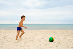 A boy playing football at the beach Royalty Free Stock Photo