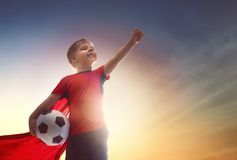 Boy playing football. Cute little child dreaming of becoming a soccer player. Boy playing football on sunset stock image