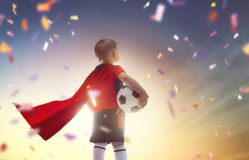 Boy playing football. Cute little child dreaming of becoming a soccer player. Boy playing football on sunset Royalty Free Stock Photo