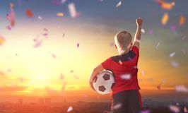 Boy playing football. Cute little child dreaming of becoming a soccer player. Boy playing football on sunset Royalty Free Stock Photography