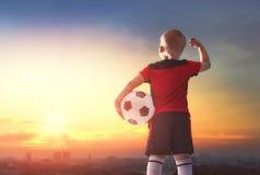 Boy playing football. Cute little child dreaming of becoming a soccer player. Boy playing football on sunset Stock Image