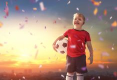 Boy playing football. Cute little child dreaming of becoming a soccer player. Boy playing football on sunset Stock Images