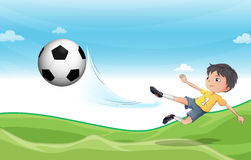 A boy playing football at the hills Stock Photography