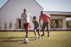 Boy playing football with his father and grandson. In garden Royalty Free Stock Photography