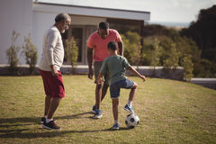 Boy playing football with his father and grandson. In garden Stock Photography